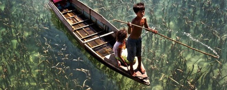 Дети катаются на лодке по кристально чистому озеру в Малайзии